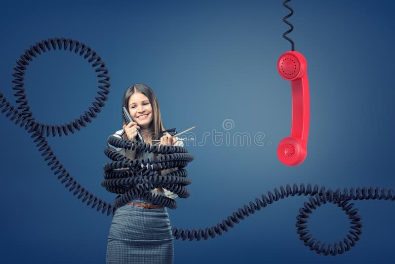 Una empresaria cogida y limitada por los cordones de teléfono negros grandes cerca de un receptor rojo gigante del teléfono imagen de archivo