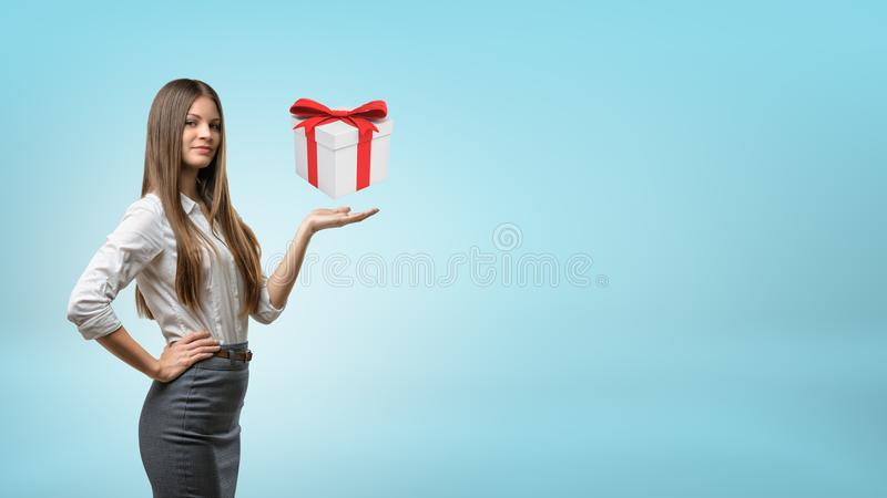 Una empresaria de pelo largo joven se coloca con una palma para arriba que apoya una caja de regalo de cernido fotografía de archivo libre de regalías