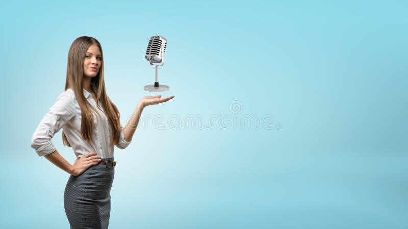 Una empresaria de pelo largo lleva a cabo hacia fuera su mano para un micrófono retro del metal fotos de archivo libres de regalías