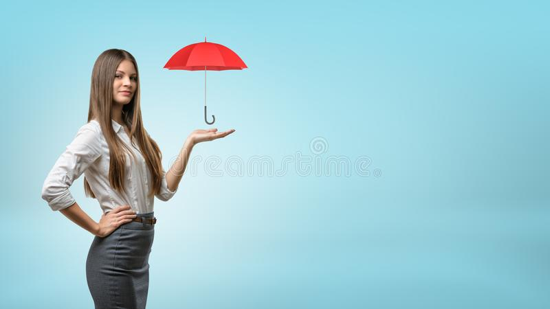 Una empresaria joven apoya un pequeño paraguas rojo abierto en su palma abierta foto de archivo libre de regalías