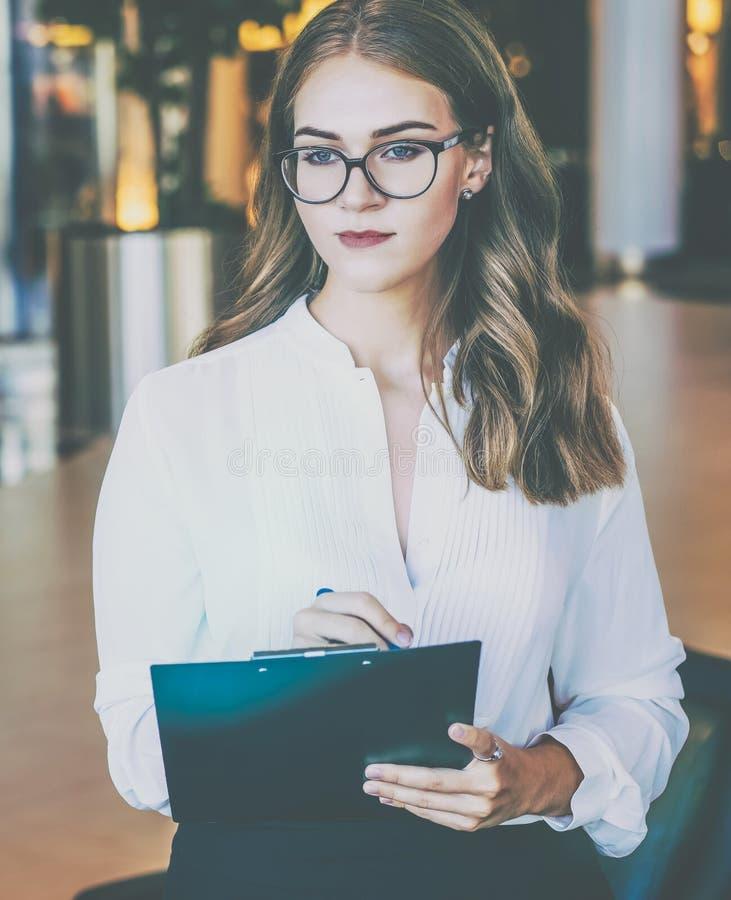 Una empresaria joven con vidrios y una camisa blanca es permanente y que sostiene un tablero La muchacha está haciendo notas fotos de archivo libres de regalías