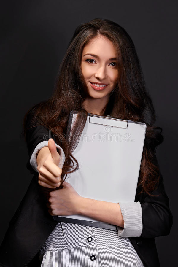 Una empresaria joven hermosa que le da los pulgares para arriba imagen de archivo libre de regalías