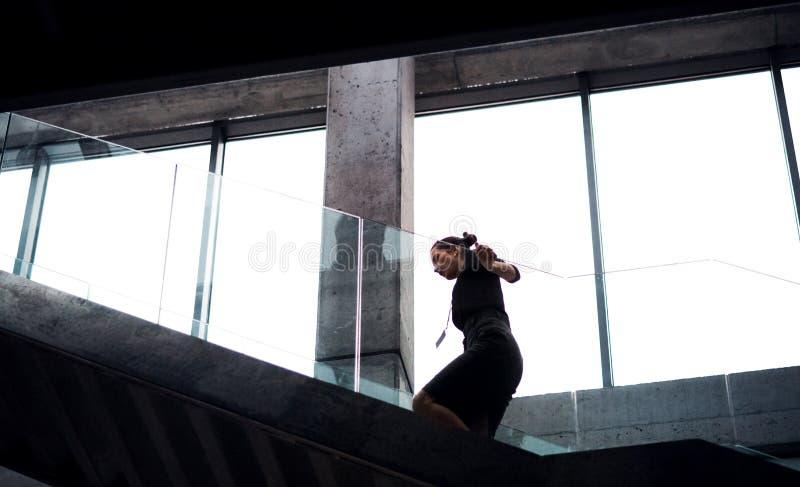 Una empresaria joven que camina encima de las escaleras en el edificio de oficinas foto de archivo libre de regalías