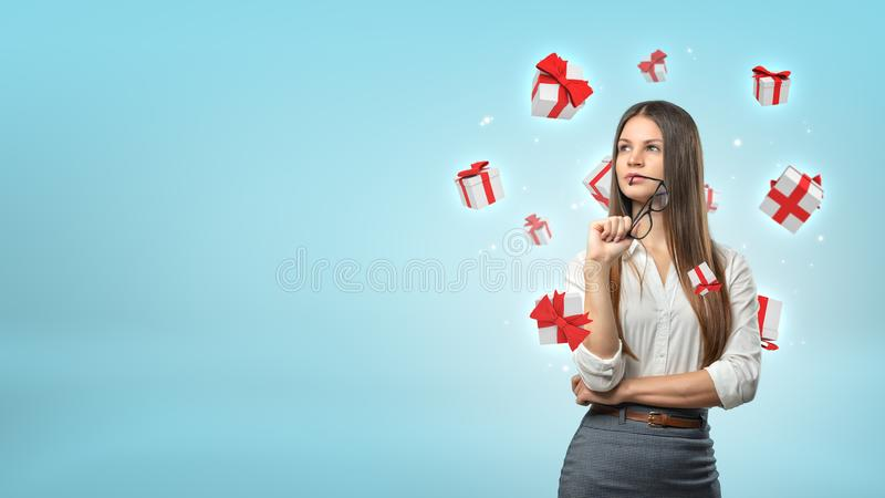 Una empresaria joven se coloca de pensamiento mientras que las pequeñas cajas de regalo blancas y rojas vuelan alrededor de su ca imagen de archivo libre de regalías