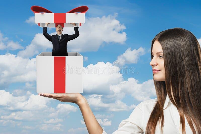Una empresaria lleva a cabo un giftbox grande con un hombre de negocios minúsculo que sale de él fotos de archivo