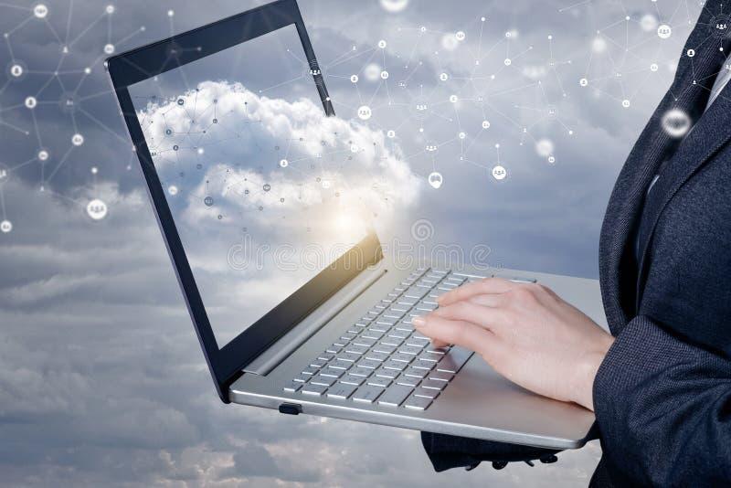 Una empresaria que trabaja con el cuaderno con las conexiones de red se nubla en él la pantalla imagen de archivo libre de regalías