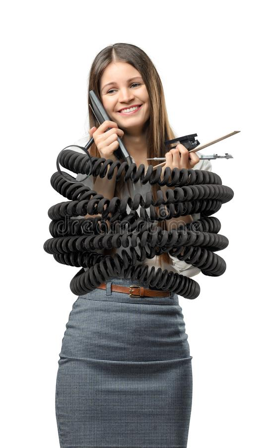 Una empresaria se coloca encuadernada por un cordón negro grande del metal y los materiales de oficina el sostenerse foto de archivo