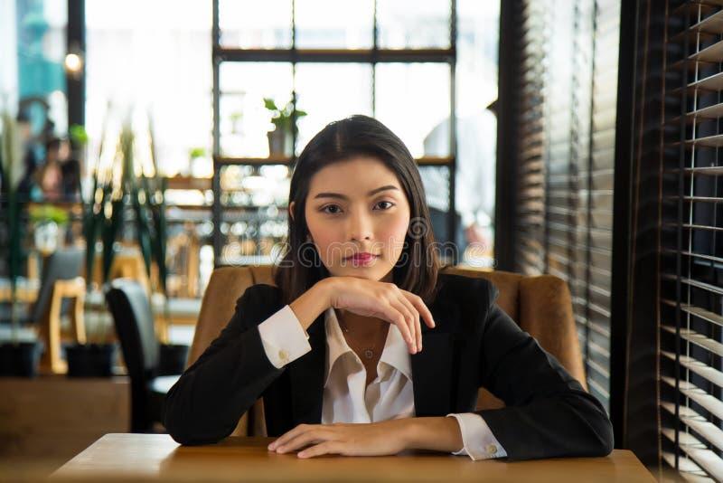 Una encantadora joven asiática vestida de forma formal, sentada en una silla de sofá marrón, puso sus manos sobre una mesa de mad foto de archivo