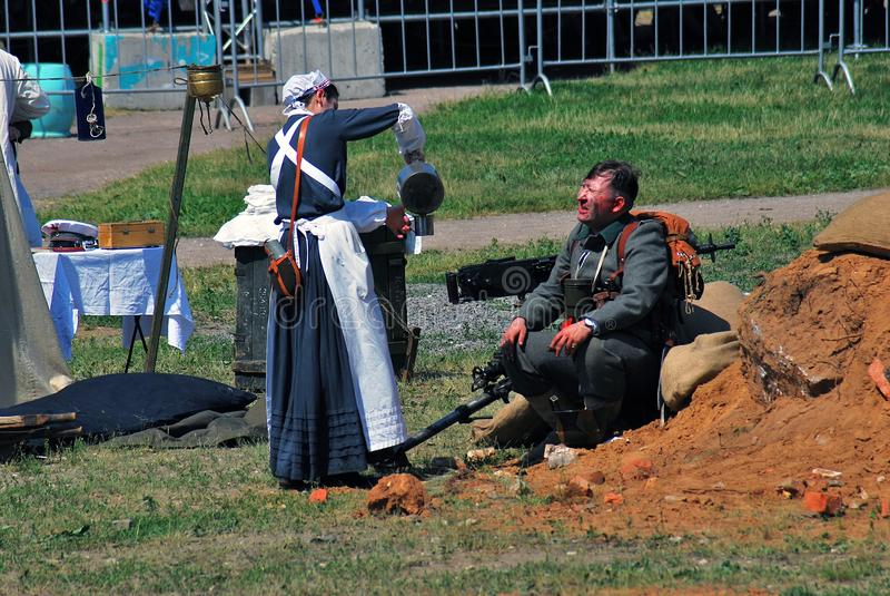 Una enfermera da el agua a un soldado, él se sienta en la tierra fotos de archivo