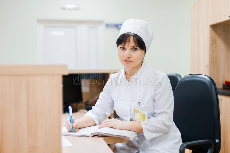 Una enfermera de sexo femenino en un vestido médico blanco se sienta en un escritorio de madera en el mostrador de recepción y ha fotos de archivo libres de regalías