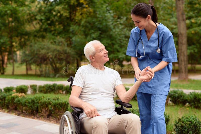 Una enfermera mide el pulso de un viejo hombre sonriente que se siente en una silla de ruedas en un parque verde foto de archivo libre de regalías