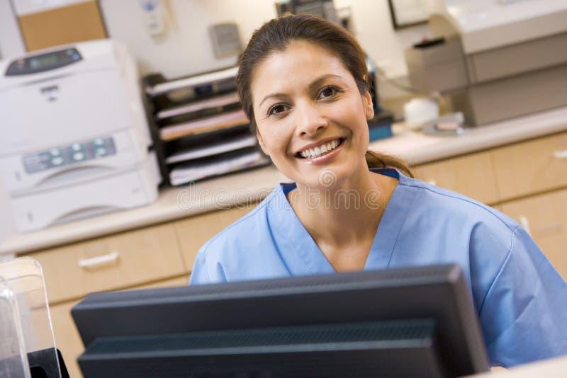 Una enfermera que se sienta en un ordenador imagen de archivo libre de regalías