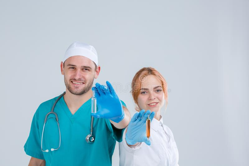 Una enfermera y un doctor en uniforme están sosteniendo una ampolla de cristal con la medicina aislamiento foto de archivo libre de regalías