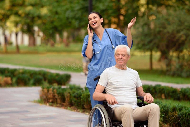 Una enfermera y un viejo hombre en una silla de ruedas están caminando en el parque Enfermera que habla en el teléfono móvil fotografía de archivo libre de regalías