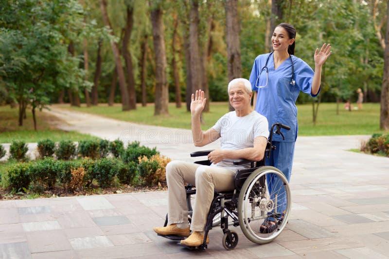 Una enfermera y un viejo hombre que se está sentando en una silla de ruedas feliz saludan alguien imagenes de archivo