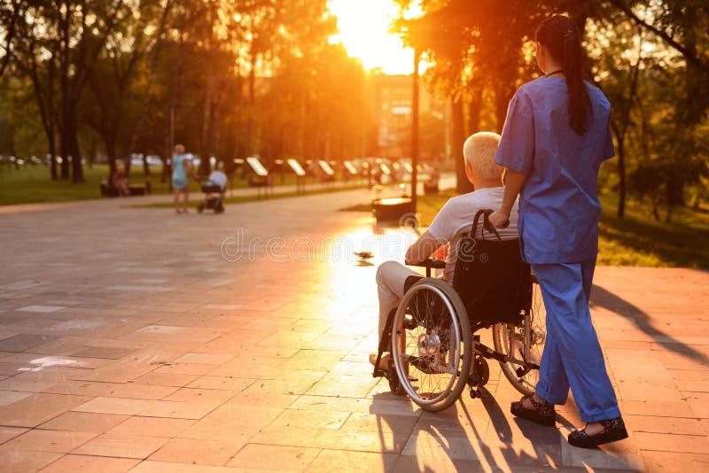 Una enfermera y un viejo hombre que se sienta en una silla de ruedas que da un paseo en el parque en la puesta del sol foto de archivo