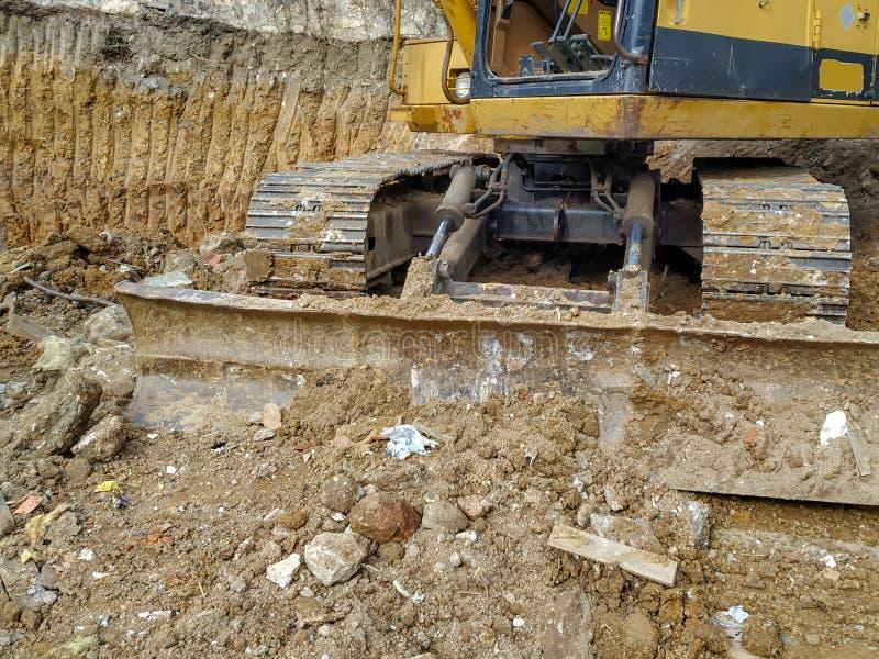 Una enorme excavadora de topadoras que trabaja entre la tierra y el barro de la excavación mientras excavan en el lugar de constr imagen de archivo