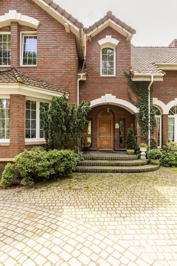 Una entrada que da la bienvenida con la puerta de madera adornada, ventanas laterales a fotos de archivo libres de regalías