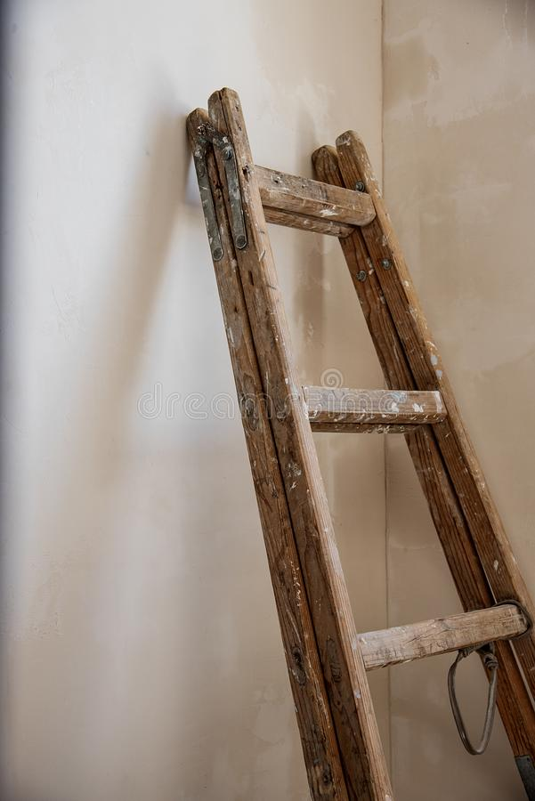 Una escalera de madera apoyada en una pared se pinta que foto de archivo libre de regalías