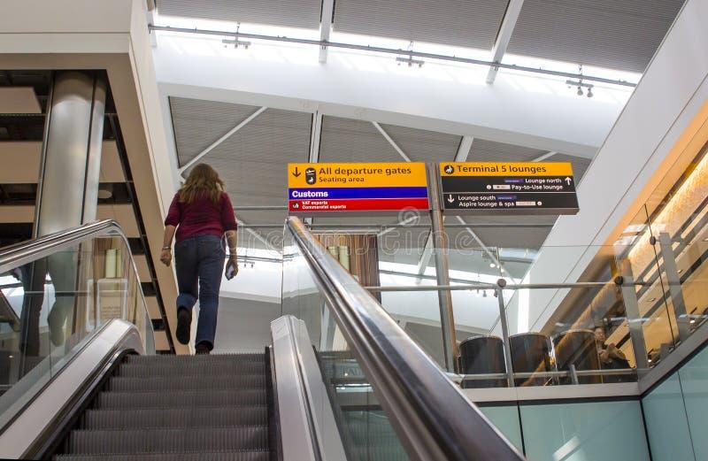 Una escalera móvil a las puertas de salida en el aeropuerto de Heathrow del terminal 5 fotos de archivo