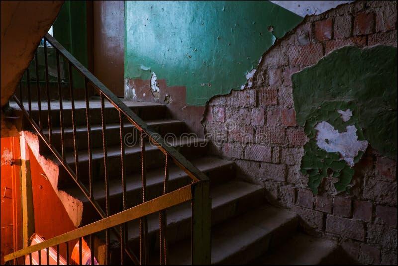 Una escalera vieja y una pared de ladrillo foto de archivo