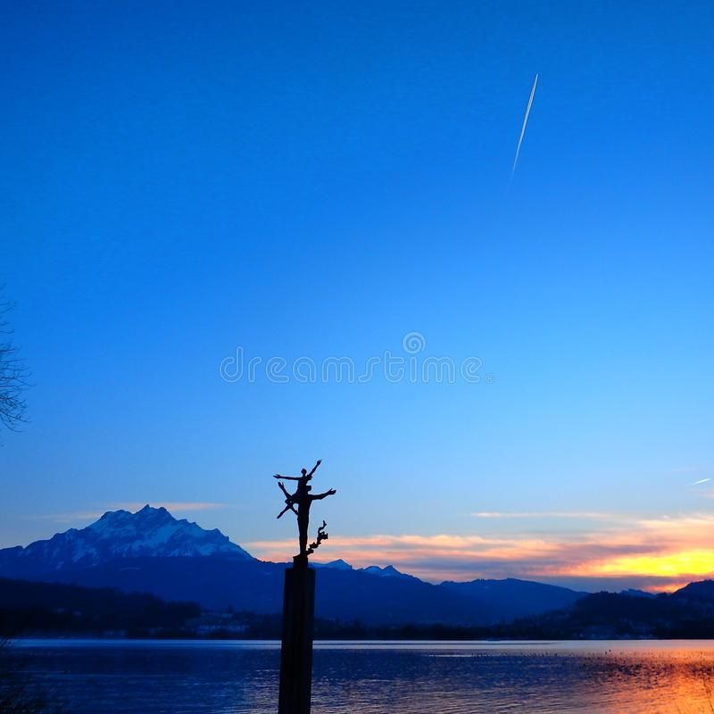 Una escena hermosa en Lucerna con un avión de pasajeros que viaja por encima fotografía de archivo
