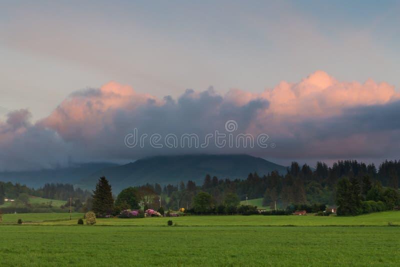 Una escena rural de granjas, de campos, y de bosques verdes en la puesta del sol debajo del rosa hermoso y de las nubes p?rpuras imagenes de archivo
