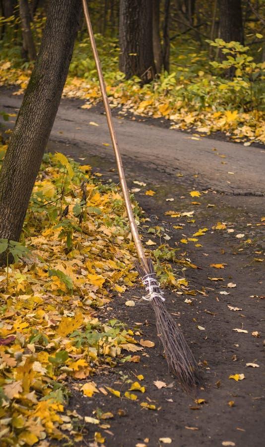 Una escoba de bruja tradicional en Halloween con las hojas secas en la tierra fotos de archivo