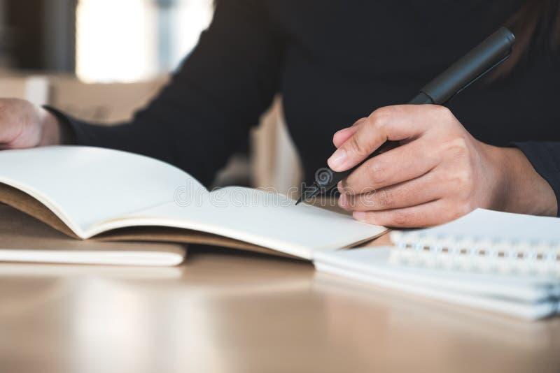 Una escritura de la mano del ` s de la mujer en los cuadernos en blanco en la tabla de madera imágenes de archivo libres de regalías