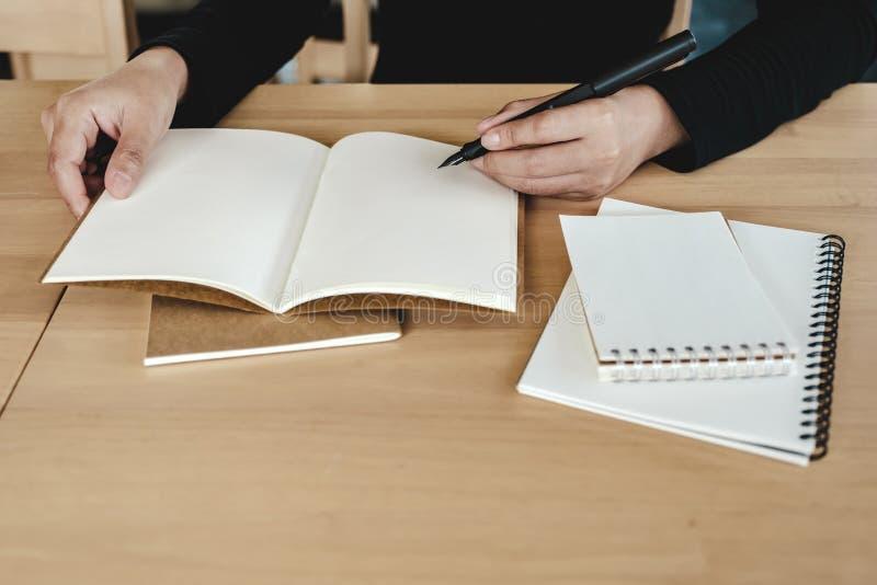 Una escritura de la mano del ` s de la mujer en los cuadernos en blanco en la tabla de madera imagen de archivo
