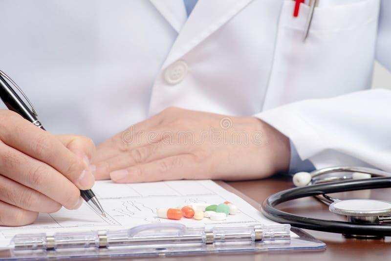 Una escritura masculina del doctor en la forma médica con el estetoscopio próximo fotos de archivo