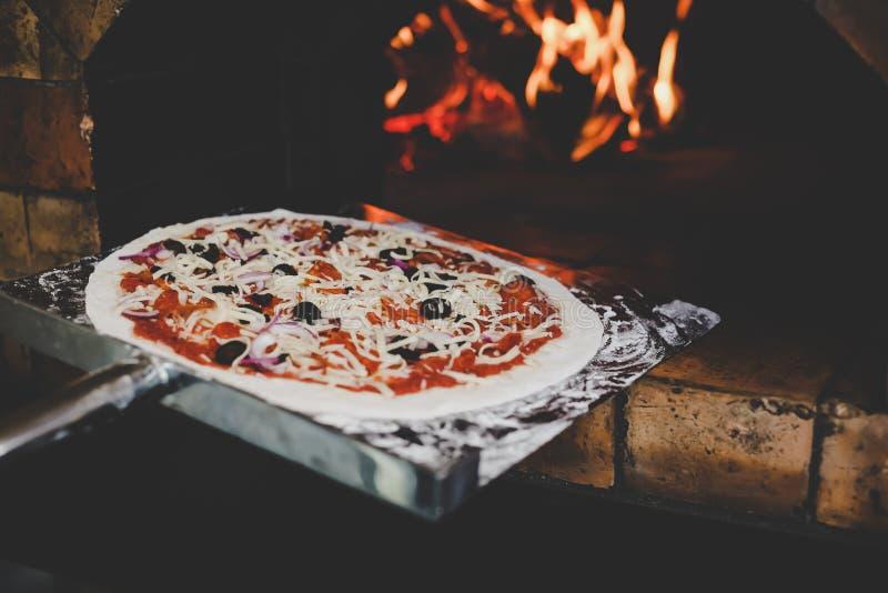 Una espátula inoxidable del uso del cocinero, puso la pizza cruda deliciosa a la estufa para la pizza cocida Comida italiana famo foto de archivo