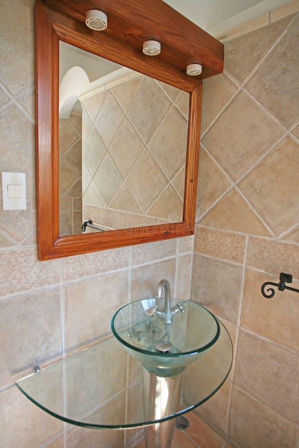 Una esquina del cuarto de baño con un espejo y un fregadero de cristal ruedan imagen de archivo libre de regalías