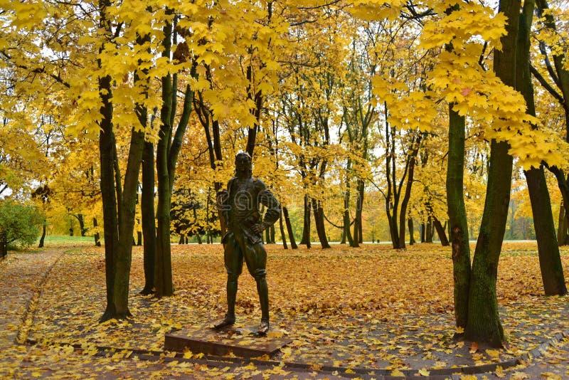 Una estatua con el follaje de otoño y los árboles amarillos foto de archivo libre de regalías