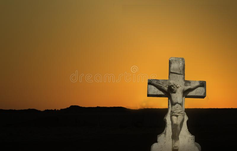 Una estatua de Jesús en la cruz en la salida del sol imagen de archivo