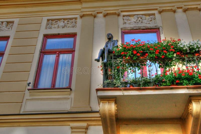 Una estatua de un muchacho que se sienta en una terraza en el viejo, histórico centro de ciudad en Presov, Eslovaquia europa imágenes de archivo libres de regalías