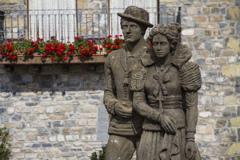 Una estatua vieja de pares jovenes delante del balcón con el flowe rojo fotos de archivo libres de regalías