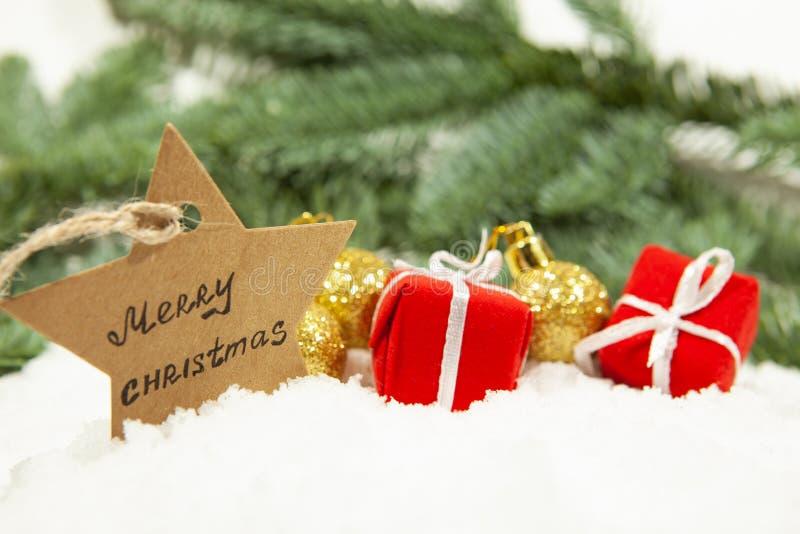 Una estrella con la Feliz Navidad y los regalos con las bolas en la nieve blanca, el concepto de la inscripción de los días de fi imagen de archivo libre de regalías