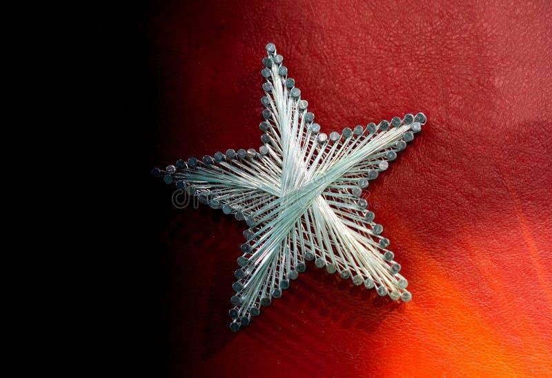 Una estrella hecha de los clavos y de la secuencia de acero en fondo rojo imágenes de archivo libres de regalías