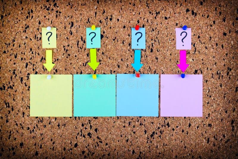 Una etiqueta engomada con un signo de interrogación se ata al tablero del corcho Etiquetas engomadas vacías para el espacio de la fotografía de archivo libre de regalías