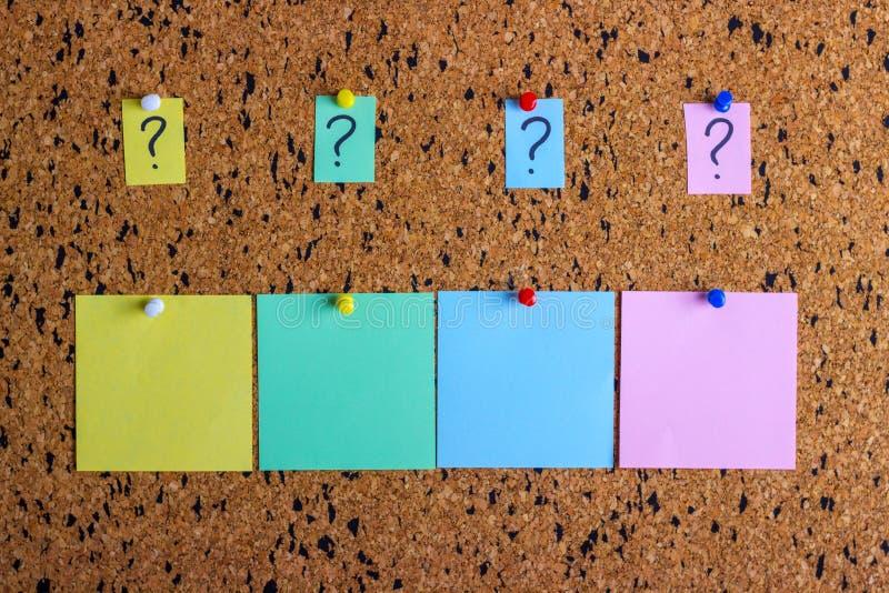 Una etiqueta engomada con un signo de interrogación se ata al tablero del corcho Etiquetas engomadas vacías para el espacio de la fotos de archivo