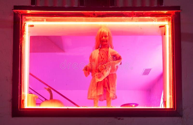Una exhibición asustadiza de la ventana de una muñeca en una ventana de la tienda, las luces de neón añade a este Halloween que m fotos de archivo libres de regalías
