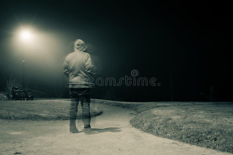Una exposición doble de una figura encapuchada fantasmal fantasmagórica situación en una trayectoria en una noche de niebla de lo fotos de archivo