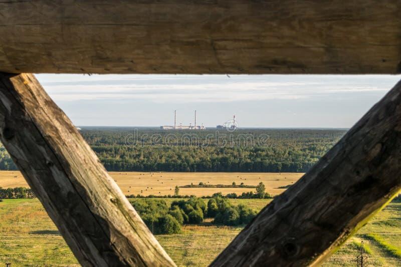 Una fabbrica con i camini in una foresta sull'orizzonte fotografie stock libere da diritti