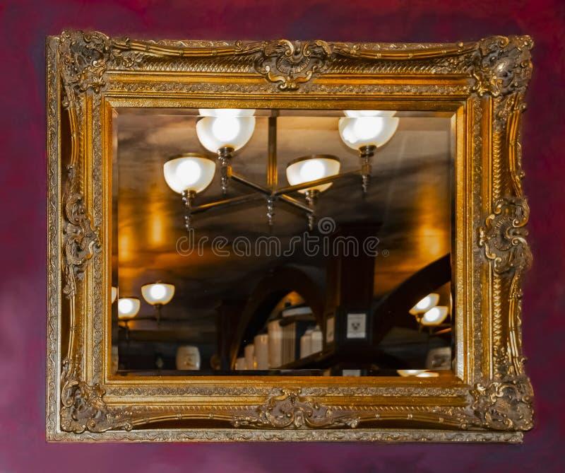 Una falsa pared marbilized pintada rojo oscuro con un espejo de oro adornado que refleja un cuarto rústico caliente con la lámpar fotografía de archivo