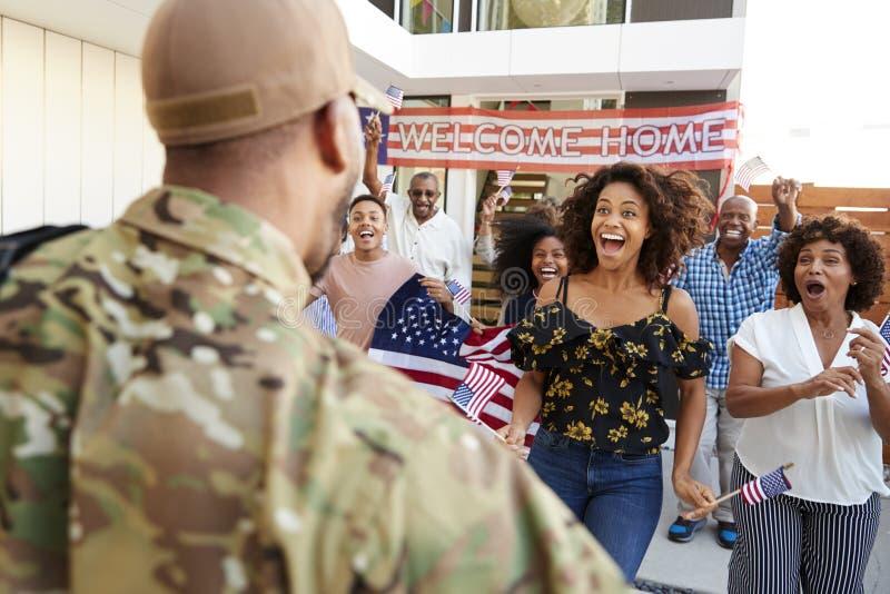 Una famiglia afroamericana di tre generazioni che accoglie favorevolmente soldato che restituisce a casa, sopra la vista della sp immagini stock