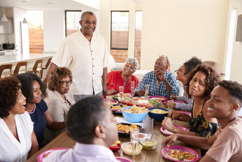 Una famiglia afroamericana di tre generazioni che si siede alla tavola di cena che celebra insieme, fine su immagini stock