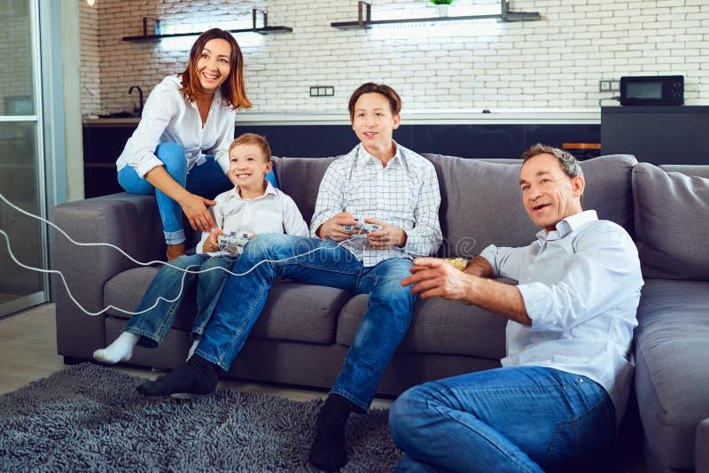 Una famiglia allegra sta giocando i video giochi mentre si sedeva su un sofà immagini stock libere da diritti