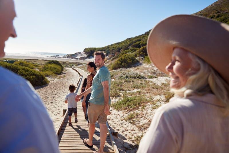 Una famiglia bianca che cammina su una spiaggia, nonni di tre generazioni nella priorità alta, sopra la vista della spalla immagini stock libere da diritti