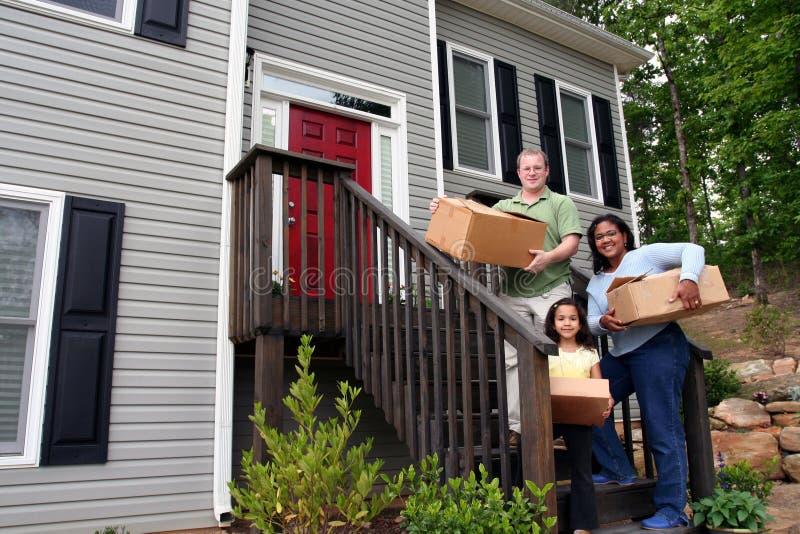 Una famiglia che entra nella nuova casa immagini stock libere da diritti